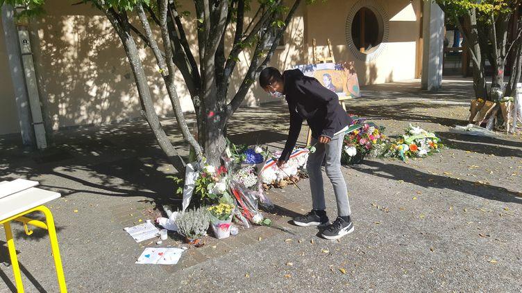 Un élève dépose une fleur lors de la cérémonie d'hommage à Samuel Paty, au collège du Bois d'Aulne à Conflans (Yvelines), où le professeur enseignait, le 16 octobre 2021. (GILLES GALLINARO / RADIO FRANCE)