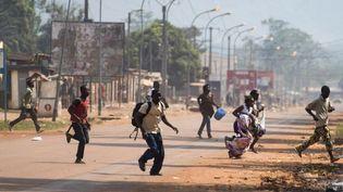 Des habitants de Bangui courent se mettre à l'abri alors que des tirs retentissent dans la capitale centrafricaine, vendredi 20 décembre 2013. (FRED DUFOUR / AFP)
