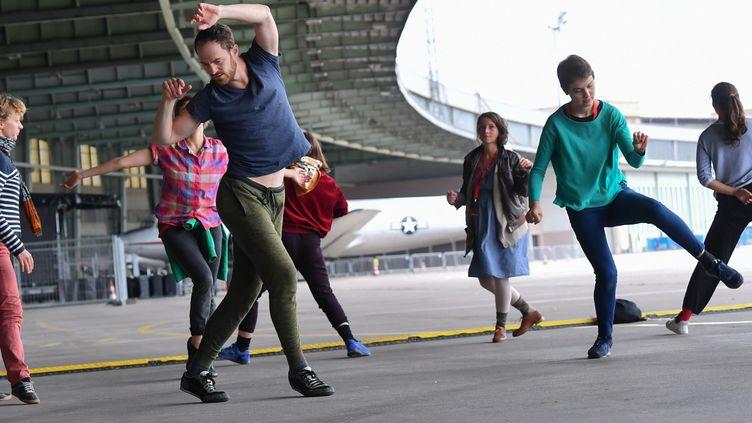 La danseur Boris Charmatz dirige une chorégraphie sur le tarmac de l'ancien aéroport de Tempelhof, à Berlin, le 7 septembre 2017.  (JENS KALAENE / DPA)