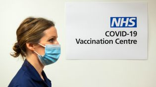 Une infirmière passe devant un panneau signalant un centre de vaccination, dans un hôpital londonien, le 7 décembre 2020. (DOMINIC LIPINSKI / AFP)