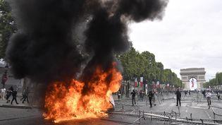 Une poubelle en flammes, dimanche 14 juillet 2019 sur les Champs-Elysées, à Paris. (JULIEN MATTIA / SPUTNIK / AFP)