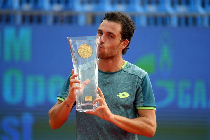 Marco Cecchinato embrasse le trophée après sa victoire en finale du tournoi ATP de Budapest (Hongrie), le 29 avril 2018. (ATTILA KISBENEDEK / AFP)