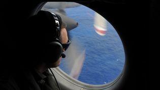 Un membre de l'aviation néo-zélandaise participe aux recherches du vol MH370, disparu début mars, au large de l'Australie, le 13 avril 2014. (GREG WOOD / AFP)