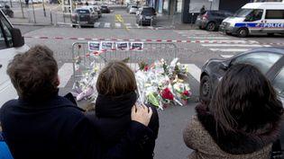 Le supermarché casher où la prise d'otage a fait quatre morts, vendredi,Porte de Vincennesà Paris, est toujours fermé. L'accès est bloqué par la police. De l'autre côté des barrières, des anonymes se recueillent. (KENZO TRIBOUILLARD / AFP)