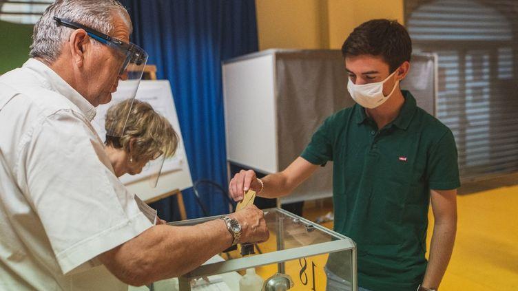 Un jeune électeur vote pour la première fois à Toulon, dans le Var, pour le premier tour des élections régionales et départementales, le 20 juin 2021. (CAMILLE DODET / HANS LUCAS / AFP)