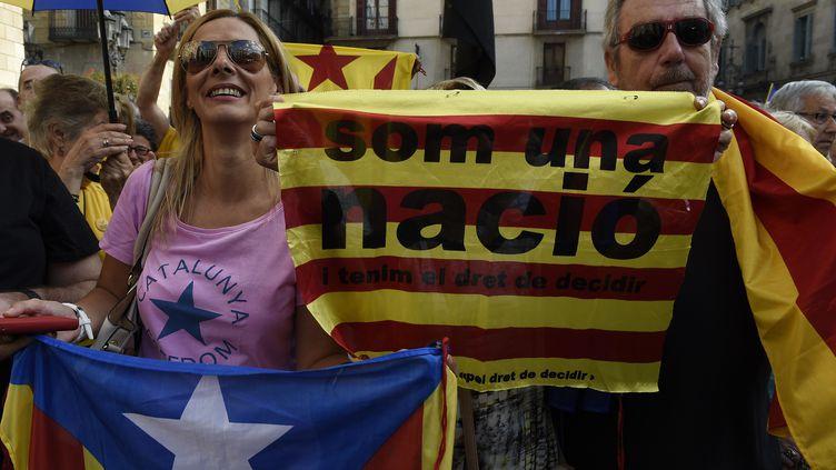 Des militants de l'indépendance catalane témoignent de leur soutien au chef du gouvernement régional Artur Mas, après la signature d'un décret ouvrant la voie à un référendum, samedi 27 septembre. (LLUIS GENE / AFP)