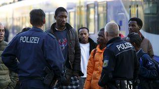 Des policiers allemands font face à des migrants arrivant en train à la gare de Munich (Allemagne), le 13 septembre 2015. (MICHAELA REHLE / REUTERS)