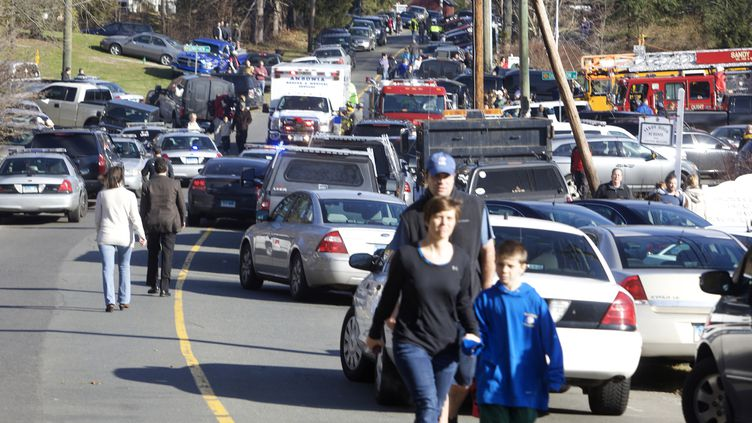 Des parents viennent chercher leurs enfants après la fusillade de l'école de Newtown (Connecticut), le 14 décembre 2012. (MICHELLE MCLOUGHLIN / REUTERS)