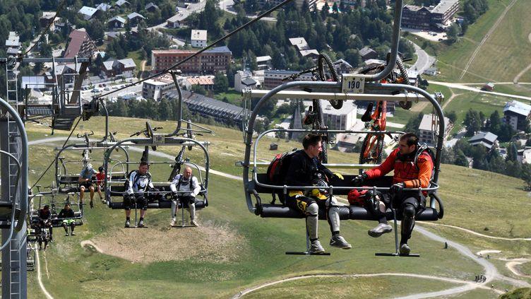 Des vacanciers aux Deux-Alpes, le 31 juillet 2017. (JEAN-PIERRE CLATOT / AFP)
