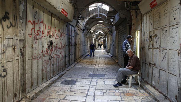 Dans la vieille ville, des habitants assis le 15 mai 2018 devant des magasins fermés lors de la grève générale en solidarité avec les Palestiniens tués la veille dans la bande de Gaza. (HAZEM BADER / AFP)