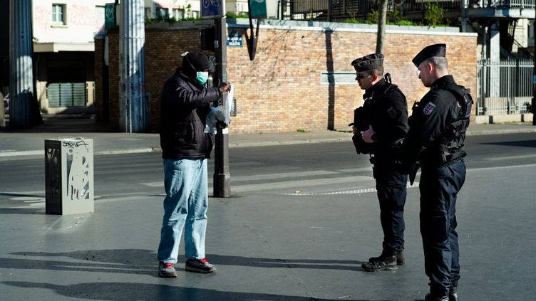 Des policiers effectuent un contrôle d'attestation de déplacement dérogatoire, le 23 mars 2020 à Paris. (EDOUARD RICHARD / HANS LUCAS)