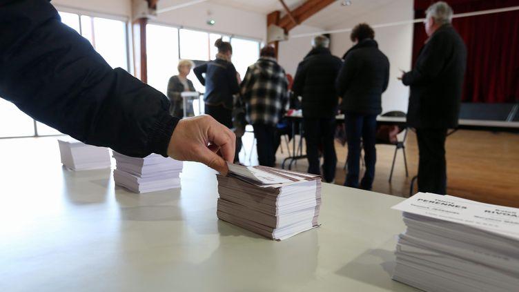 Un électeur saisit des bulletins de vote, à Plouëc-du-Trieux (Côtes-d'Armor), lors du premier tour des élections départementales, dimanche 22 mars 2015. (  MAXPPP)