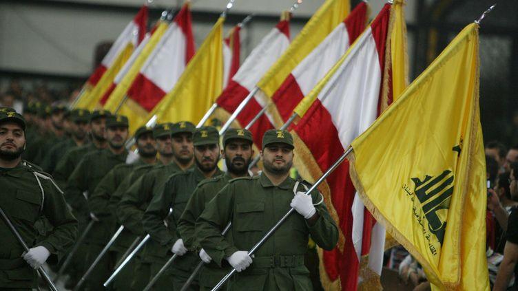 Des combattants du Hezbollah portent le drapeau libanais et le drapeau jaune du mouvement chiite à l'occasion du Jour des martyrs, à Beyrouth (Liban), le 11 novembre 2009. (RAMZI HAIDAR / AFP)