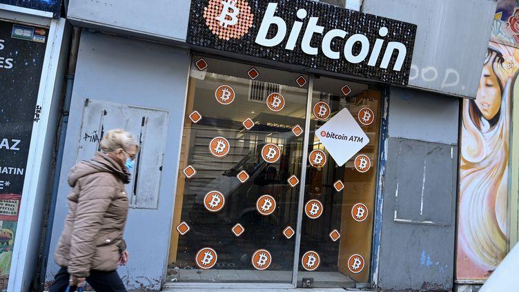 Une femme passe devant la vitrine d'un magasin spécialisé dans le bitcoin, à Marseille, le 8 janvier 2021. (NICOLAS TUCAT / AFP)