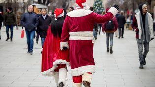 Un couple habillé en mère et père Noël,àPristina (Kosovo), le 25 décembre 2017. (ARMEND NIMANI / AFP)