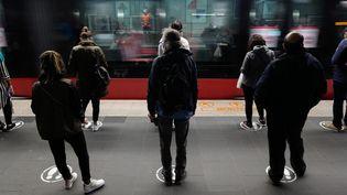 Des voyageurs attendent sur un quai de tramway, en respectant les repères peints au sol,le 11 mai 2020 à Nice (Alpes-Maritimes). (VALERY HACHE / AFP)