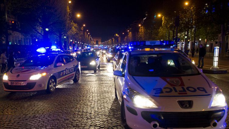 """Des policiers manifestent sur les Champs-Elysées contre la mise en examen pour """"homicide volontaire"""" d'un de leurs collègues, à Paris, le 25 avril 2012. (BERTRAND LANGLOIS / AFP)"""