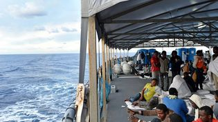 Des migrants et réfugiés africains, dont beaucoup de Sénégalais, après avoir été secourus en mer, se reposent sur le navire de la marine allemande Werra, le 27septembre 2015.  (ALBERTO PIZZOLI/AFP)