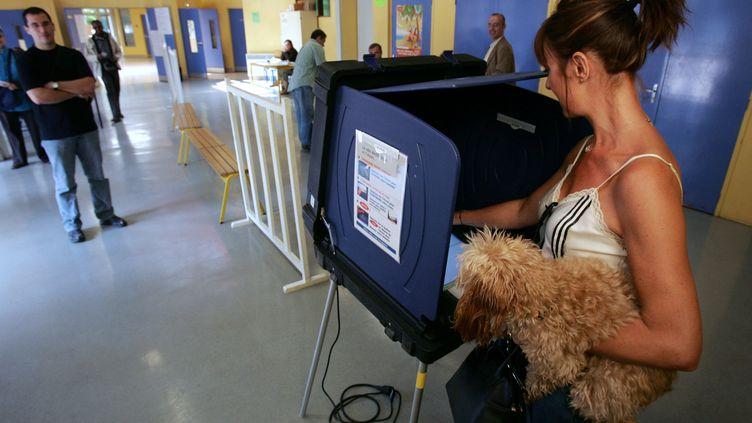 Une électrice utilise une machine à voter à Issy-les-Moulineaux (Hauts-de-Seine), lors du second tour d'une précédente élection présidentielle, le 6 mai 2007. (PIERRE VERDY / AFP)