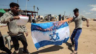 Des palestiniens font brûler un drapeau israélien dans la bande de Gaza à Khan Younis, le 9 avril 2018. (SAID KHATIB / AFP)