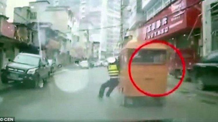 Capture d'écran montrant le policier accrochéà un pusse-pousse dans les rues deLichuan, en Chine (TITANVORTEX / YOUTUBE)