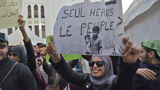 """""""Un seul héros le peuple"""" est un slogan célèbre en Algérie issu de cette photo historique prise à Alger en juillet 1962 et brandie par cette manifestante, le 5 mars, à Alger. (RYAD KRAMDI / AFP)"""