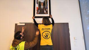 Des militants écologistes décrochent le portrait d'Emmanuel Macron de la mairie de Saint-Sébastien-sur-Loire (Loire-Atlantique), le 4 mars 2019. (LOIC VENANCE / AFP)