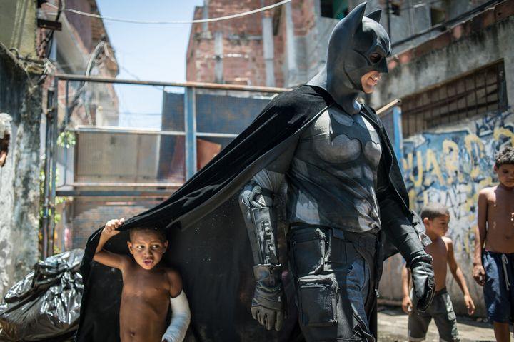 Des enfants de la favela de Metrô-Mangueira, à Rio de Janeiro (Brésil), posent avecEron Morais de Melo, un militant déguisé en Batman, qui proteste contre la destruction de maisons dans le cadre des travaux de la Coupe du monde de football, le 9 janvier 2014. (YASUYOSHI CHIBA / AFP)