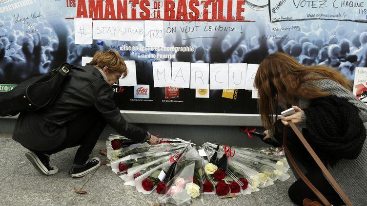 """Deux femmes déposent des fleurs devant l'affiche du spectacle """"1789 Les amants de la Bastille"""", au Palais des sports de Paris, le 9 novembre 2013. (KENZO TRIBOUILLARD / AFP)"""