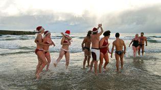 Déjà en 2004, des courageux respectent le rituel du bain du 25 décembre sur la plage de Collignon à Tourlaville (Manche). (MYCHELE DANIAU / AFP)