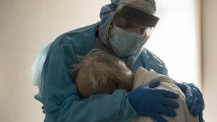 Le Dr Joseph Varon réconforte dans ses bras un patient atteint du Covid-19 dans une unité de soins intensifs del'hôpital United Memorial de Houston, au Texas (Etats-Unis), le 26 novembre 2020. (GO NAKAMURA / GETTY IMAGES NORTH AMERICA / AFP)