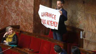 LedéputéSébastien Nadot brandit une bannière à l'Assemblée nationale, le 19 février 2019. (JACQUES DEMARTHON / AFP)