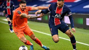 Kylian Mbappé (PSG) à la lutte avec Pedro Mendes (Montpellier), le 22 janvier 2021. (FRANCK FIFE / AFP)