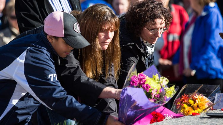 Des personnes déposent des fleurs en hommage àNathan Cirillo, lors d'une cérémonie, le 24 octobre 2014 à Ottawa (Canada). (ANDREW BURTON / GETTY IMAGES NORTH AMERICA / AFP)