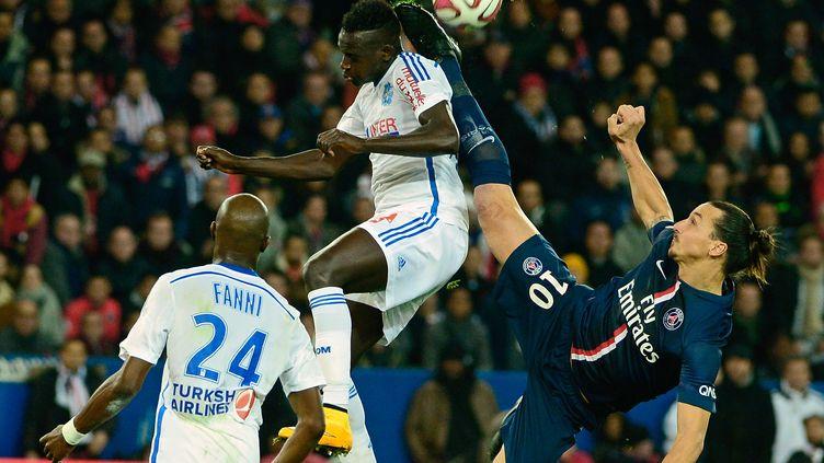 L'attaquant du Paris Saint-Germain, Zlatan Ibrahimovic, aux prises avec le défenseur marseillais, Benjamin Mendy, le 9 novembre 2014. (MIGUEL MEDINA / AFP)