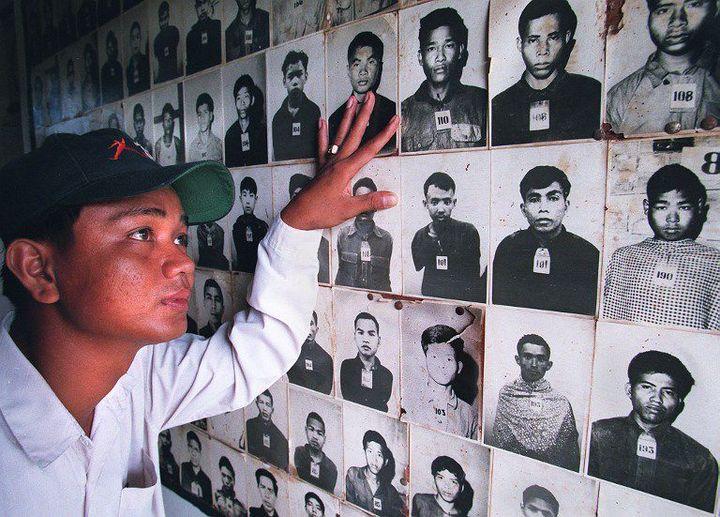 Eng Rottha, 28 ans, regarde des photos de personnes torturées et massacrées par des Khmers rouges dans l'ancienne prison de Tuol Sleng à Phnom Penh, devenue un musée. Un lieu de supplice oùsont morts12.380 adultes et enfants. Dont le propre père d'Eng Rottha. (AFP - ROB ELLIOTT)