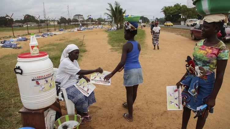 (Une femme distribue des informations sur le virus Ebola, au Liberia, le 12 août. © MaxPPP)
