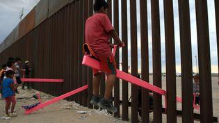 """Des enfants mexicains et américains font ensemble de la balançoire, malgré le mur qui sépare leurs deux pays. Cette oeuvre, """"The Teeter Totter Wall"""" a reçu le prixBeazley 2020 du design. (LUIS TORRES / AFP)"""