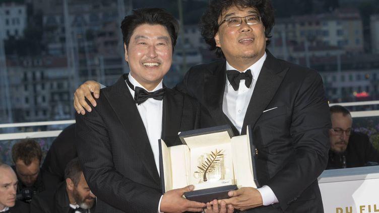 Le réalisateur sud-coréen Bong Joon-ho (à droite) prend la pose avec sa Palme d'Or aux côtés de l'acteur Song Kang-ho, samedi 25 mai 2019 à Cannes (Alpes-Maritimes). (BOESL / DPA / AFP)