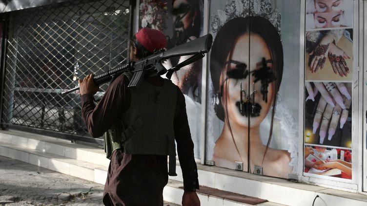 Un combattant taliban passe devant un salon de beauté vandalisé à Kaboul, le 18 août 2021. (WAKIL KOHSAR / AFP)