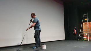 Emmanuel Bizot, fils de Léonie et gérant du cinéma, en train de repeindre la scène. (Boris Loumagne / Radio France)