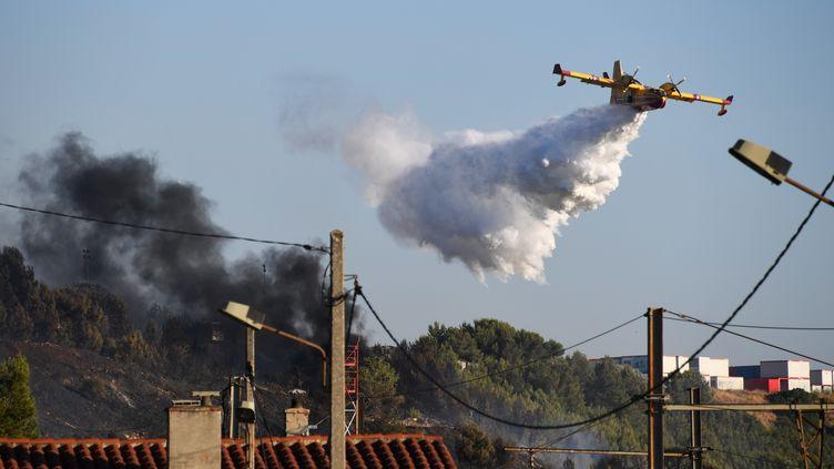 Un Canadair survole la zone de Vitrolles (Bouches-du-Rhônes) oùun incendie s'est déclaréle 10 juillet 2019. (CHRISTOPHE SIMON / AFP)