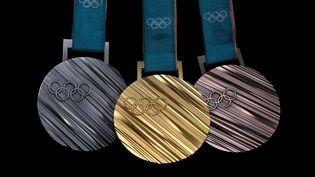 Les médailles d'or (au dentre), d'argent (à gauche) et de bronze distribuées aux Jeux olympiques d'hiver 2018 de Pyeongchang (Corée du Sud). (LUCY NICHOLSON / REUTERS)