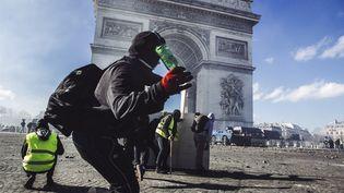 Un manifestantcagoulé s'apprête à lancer une bouteille sur les forces de l'ordre, devant l'Arc de triomphe à Paris, le 16 mars 2019. (YANN CASTANIER / HANS LUCAS / AFP)