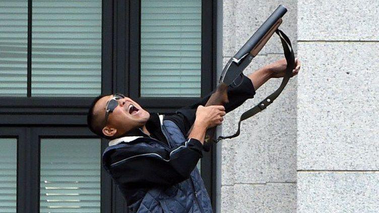 A Tokyo, le 5 juillet 2015, un homme prend part à des exercices anti-terroristes, en tenant un fusil sur un balcon de la Diète nationale, où est situé le Parlement. (TOSHIFUMI KITAMURA / AFP)
