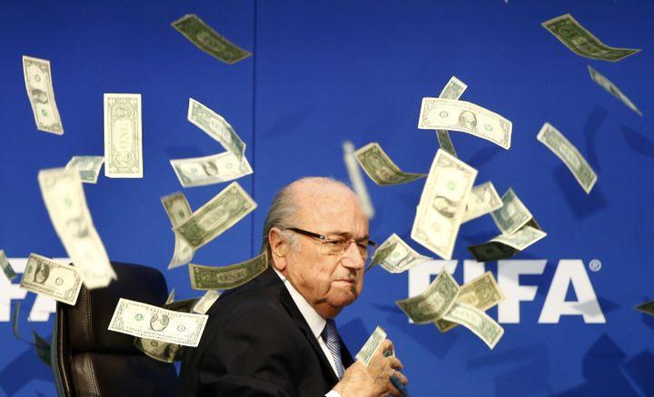 Le président de la Fifa, Sepp Blatter, couvert de faux billets lancés par un humoriste britannique, le20 juillet 2015, à Zurich (Suisse), avant une conférence de presse. (ARND WIEGMANN / REUTERS)