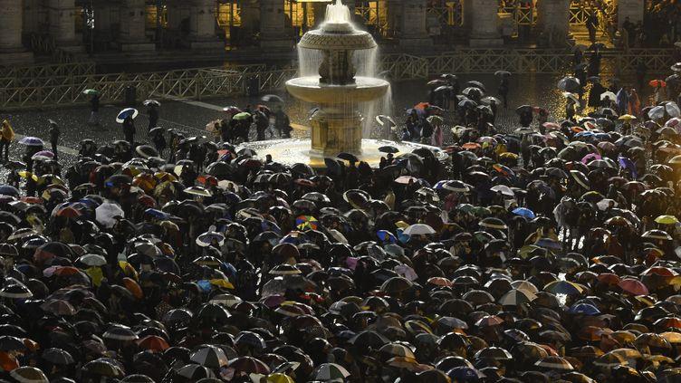 La foule se rassemble place Saint-Pierre au Vatican, le 13 mars 2013, alors que de la fumée blanche s'échappe de la chapelle Sixtine. (FILIPPO MONTEFORTE / AFP)