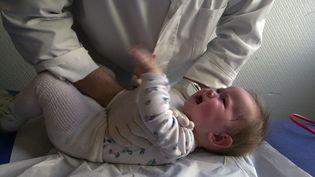 Un kinésithérapeute effectue, le 03 novembre 2003, un massage respiratoire sur un bébé de neuf mois atteint par la bronchiolite, une maladie des bronches due à un virus et qui touche chaque hiver près de 30 % des nourrissons. (MYCHELE DANIAU / AFP)