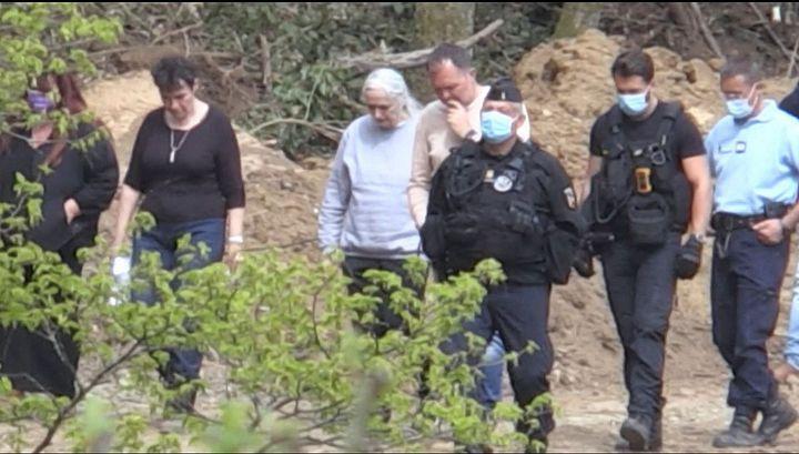 Monique Olivier, l'ex-femme de Michel Fourniret, entourée des enquêteurs dans le bois d'Issancourt-et-Rumel (Ardennes), le 28 avril 2021. (THOMAS BERNARDI / AFP)