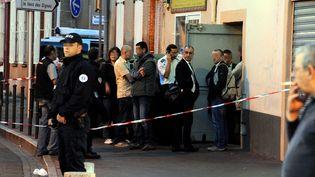 Des policiers devant la supérette de Toulouse (Haute-Garonne) où un jeune braqueur a été abattu par un policier, le 17 octobre 2014. (  MAXPPP)